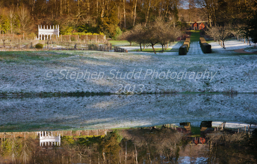 Painswick Rococo Garden, Gloucestershire, view across pond to Exedra and Red House both reflected in pond