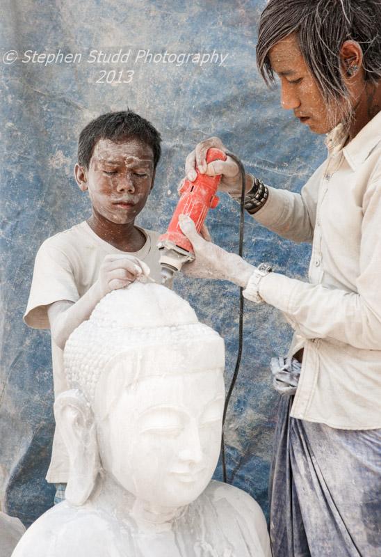 Mandalay stonemasons quarter boy and young man carving Buddha statue Burma Myanmar