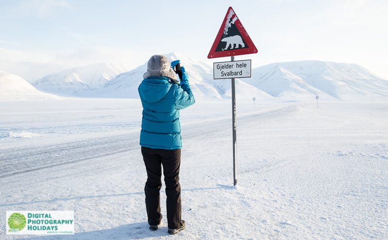 Arctic circle, North polar region, Europe, Scandinavia, Norway, Svalbard, Spitsbergen,  Longyearbyen, woman photographing beware of polar bears sign in Adventdalen valley