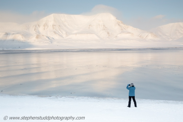 Arctic circle, North polar region, Europe, Scandinavia, Norway, Svalbard, Spitsbergen, view from Longyearbyen towards Hiorthfjellet mountain across Adventfjorden fjord, Advent Bay, woman taking photo across the bay