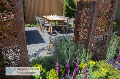 Photographer: Stephen Studd - The Urban Flow Garden: laser cut steel pillars, brick paved patio area with dining table and chairs, Lupinus 'Masterpiece' - Designer: Tony Woods - Sponsor: Thames Water