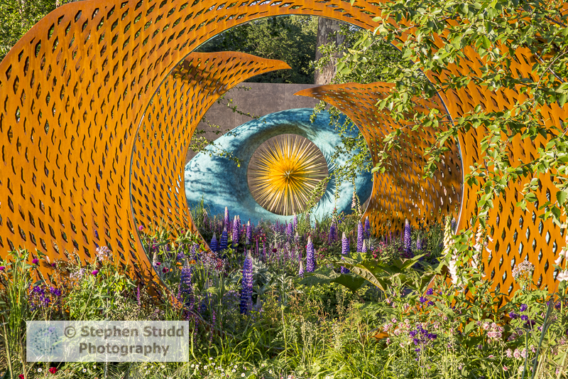 Photographer: Stephen Studd - The David Harber and Savills garden, view through corten rusted steel screens towards the Aeon sculpture, planted with Lupinus 'Persian Slipper', Aquilegia 'Blue Barlow', Aquilegia 'Nora Barlow' - Designer: Nic Howard - Spon