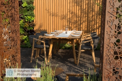 Photographer:Stephen Studd - The Urban Flow Garden: laser cut corten steel pillars, edible vertical wall planted with lettuce, herbs and nasturtium, brick paved patio with table and chairs, wood panel garden wall - Designer: Tony Woods - Sponsor: Thames Water