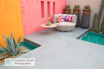 Photographer:Stephen Studd - Beneath A Mexican Sky garden, view of turquoise pool with Stenocereus marginatus cactus and container with Agave americana grown in gravel, orange and red, polished concrete floating patio with chair with floral prints, table with succulent growing in atrium - Designer: Manoj Malde - Sponsor: Inland Homes PLC