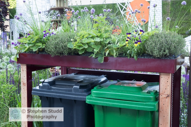 Photographer: Stephen Studd  -  The RHS Greening Grey Britain Garden, Wheelie bins for household rubbish and green wheelie bin for recycling with a living roof cover planted with edible plants and herbs, viola, chives, strawberries, thyme, sage and mint, drilled wood panels for insect hotel, Designer: Professor Nigel Dunnett
